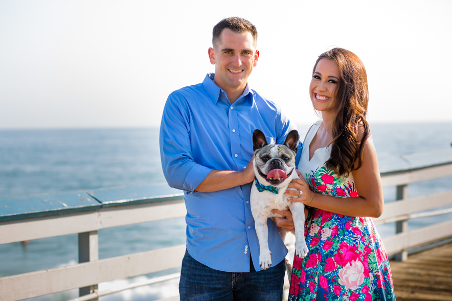 couple holds their french bulldog on the pier
