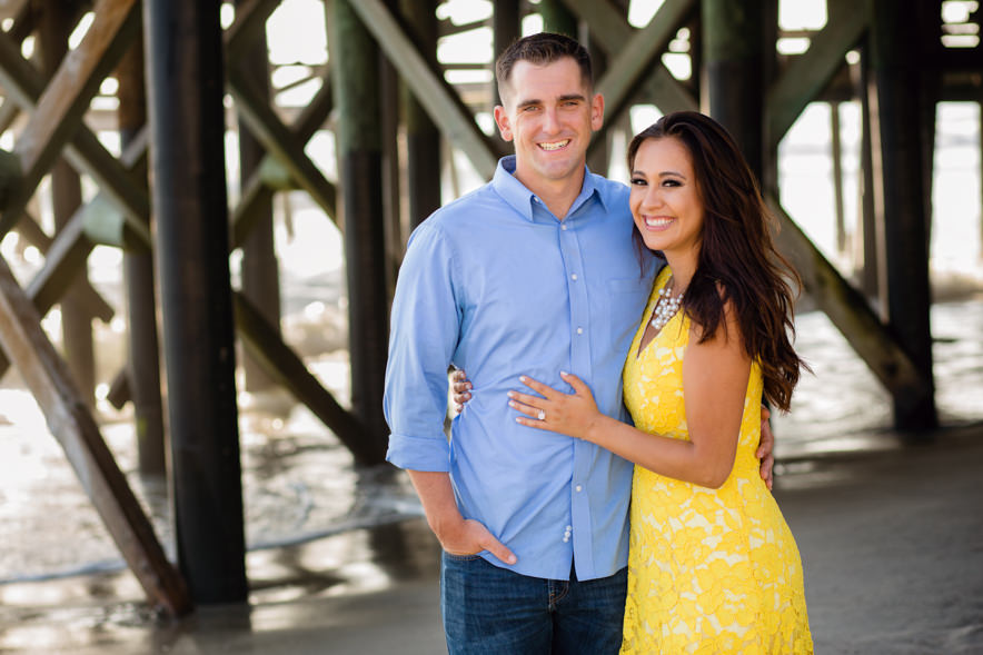 the couple smiles at the camera under the san clemente pier