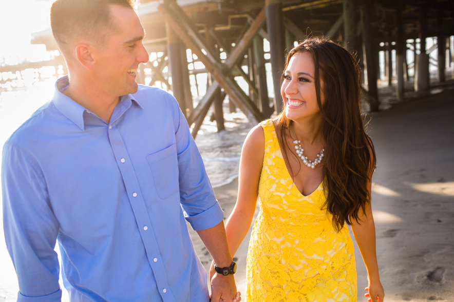 couple walks on the beach and laughs with each other
