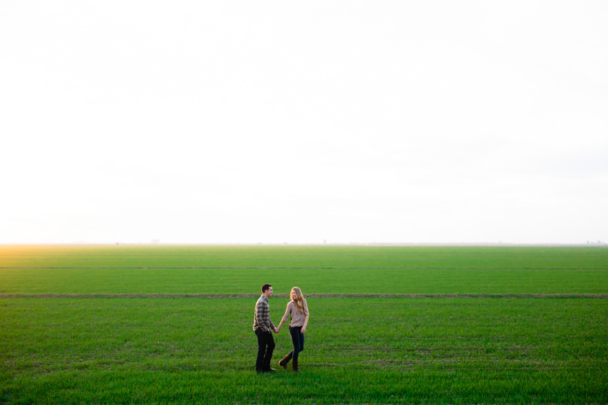 couple walks in an open green field during barn engagement session