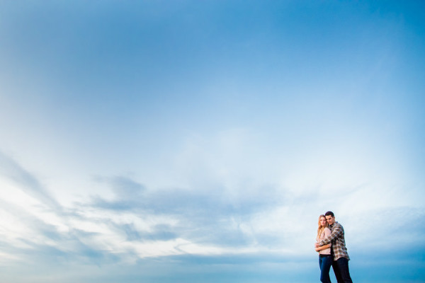 engaged couple against a big blue sky