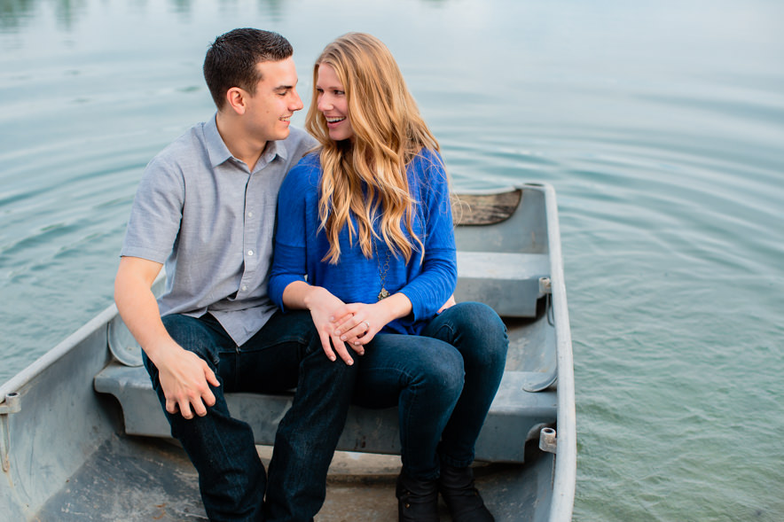 engaged couple sits together in a boat in the lake