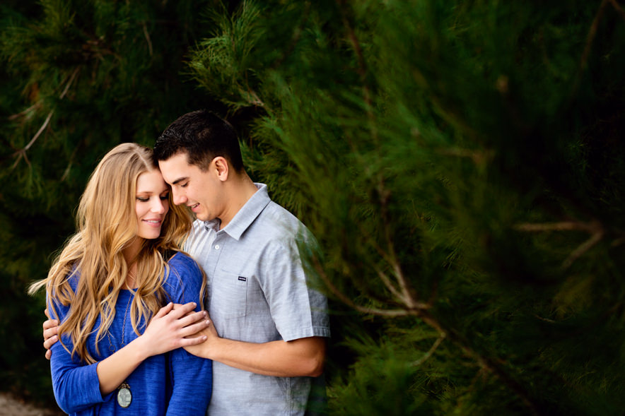 engaged couple holds each other near a forest of trees