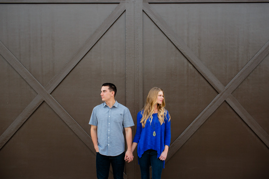 engaged couple poses together in front of barn doors for a barn engagement session